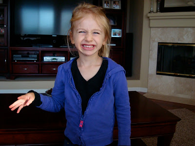 Child standing in front of coffee table with arm out smiling