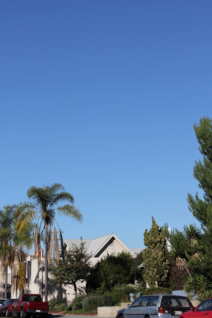 Blue sky over house with trees and cars on street