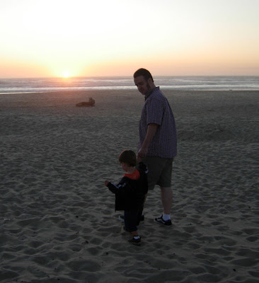 papa and boy on the beach at sunset