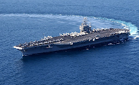 Aircraft carrier USS John C. Stennis making a sharp clockwise U-turn on the deep blue ocean. Picture by Tina Lamb, USN