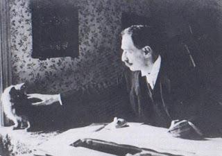 Louis Wain (1860-1939) dibujando con uno de sus gatos en la mesa