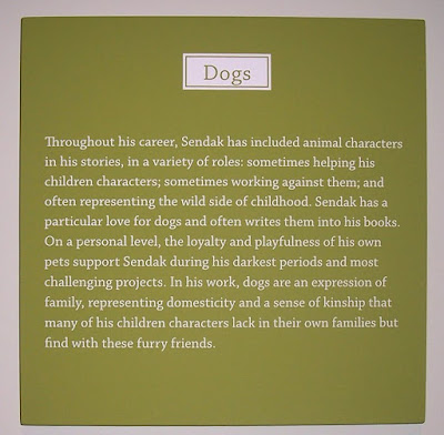 sign from museum that talks about sendak's love for dogs, text says, Throughout his career, Sendak has included animal characters in his stories, in a variety of roles:  sometimes helping his children characters; sometimes working against them; and often representing the wild side of childhood.  Sendak has a particular love for dogs and often writes them into his books. On a personal level, the loyalty and playfulness of his own pets support Sendak during his darkest periods and most challenging projects. In his work, dogs are an expression of family, representing domesticity and a sense of kinship that many of his children characters lack in their own families but find with these furry friends.