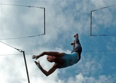 athletic-looking fellow in mid air, going from one trapeze to the next