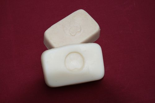 two bars of creamy soap embellished with a pawprint