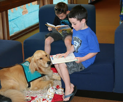two young boys about 5 years old, sit in blue chairs reading books, while Penny lays at their feet on a blanket