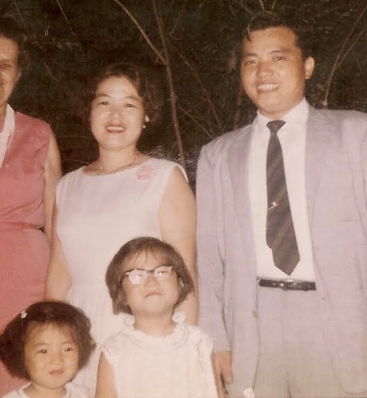 old and faded photo of my mom and dad in back row, my sister wearing glasses in the front, and me, barely tall enough to make it into the photo