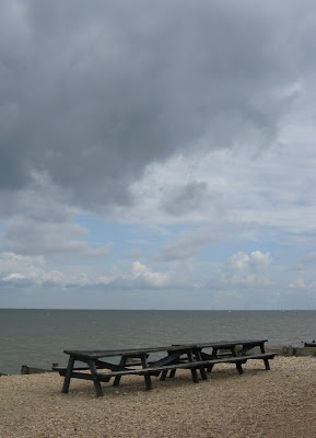 Grey clouds above a pub bench on the beach