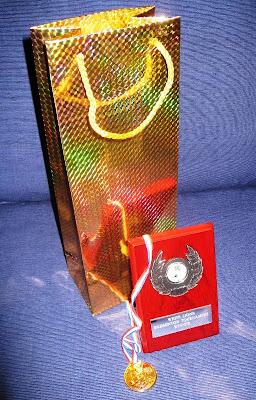 Medal, trophy and sparkly wine bag