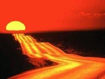 Fotografía en la que se muestra una amplia carretera que atraviesa el desierto en dirección al sol que se pone en el horizonte