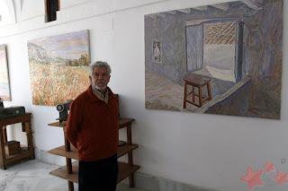 Antonio R. Agüera frente a sus obras [Foto: Manuel Ramírez Ordóñez, web Pintores de Ubrique]