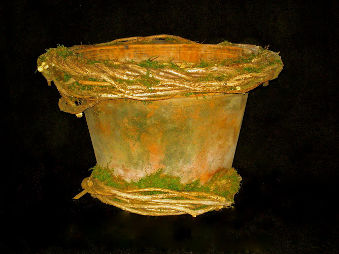 Aged terracotta pot wrapped in bittersweet and moss