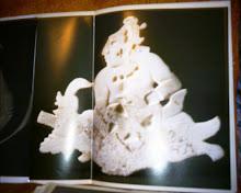 Talla representando a un maya que sostiene una especie de navio acuático
