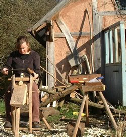 Transition Housewife making a stool leg using a shaving horse and draw-knife