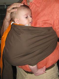 Μωράκι σε μάρσιππο αγκαλιάς - sling - στην καθιστή θέση με τα πόδια έξω.