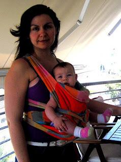 Με το μωρό στο μάρσιπο αγκαλιάς mei tai, να κοιτάζει μπροστά (έξω), με τα πόδια έξω.