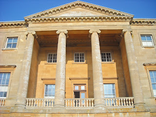 Front facade of Basildon Park, stone discoloured on sides of ionic columns and pediment, crumbling on columns and lichens growing