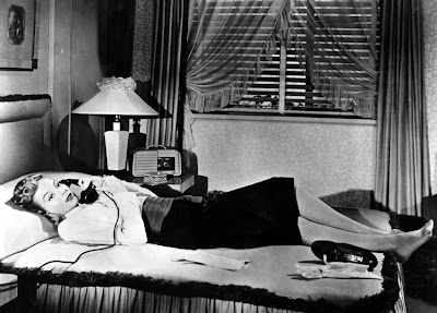 Evelyn Keyes relaxes while phoning.