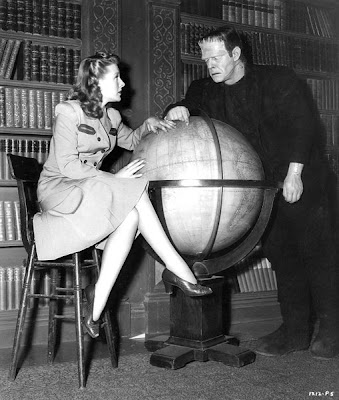 Evelyn Ankers and the Frankenstein monster examine a globe.
