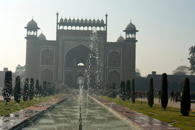 A diffused view of the outer gate of the Taj Mahal compound and a water fountain