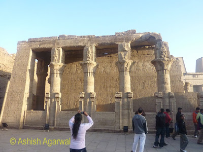 Edfu temple in Egypt - tourist taking a photo of some of the pillars