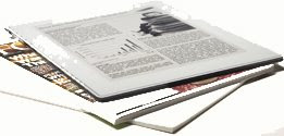 picture of Plastic Logic reader with magazines and a pad of paper