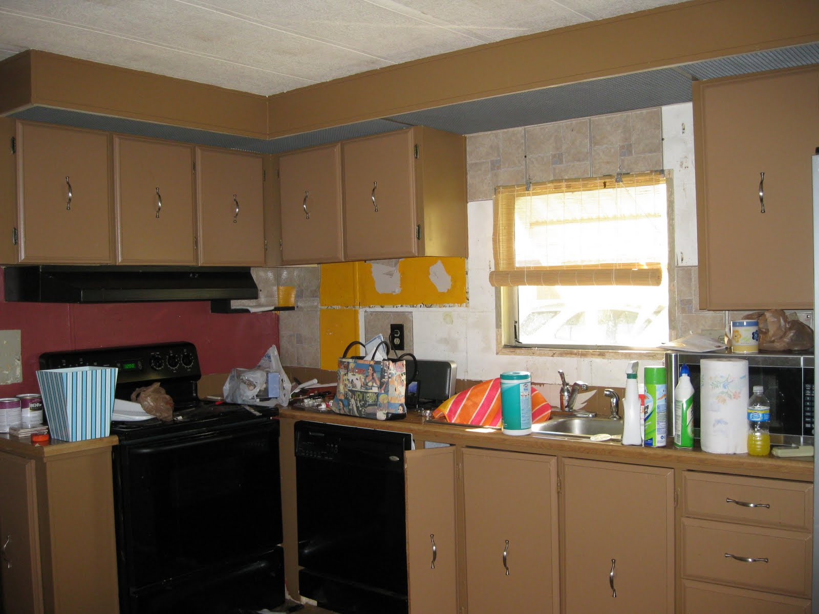 is another view of the kitchen with a dark red wall. Not my style
