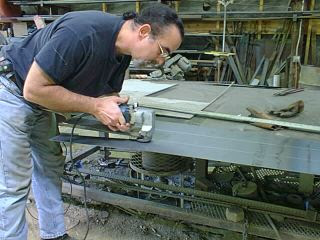 Man cutting lead sheets to put up as a barrier against Internet piggybackers