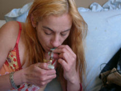 Woman smoking crack with ye olde crack pipe