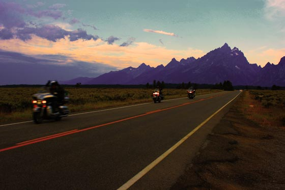 Motorcycles riding through Grand Teton National Park early in the morning.