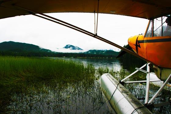 A yellow Juneau, Alaska seaplane docked on a small lake.