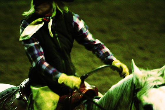 A Denver stock show cowgirl riding a horse and wearing flannel at the National Western Stock Show.