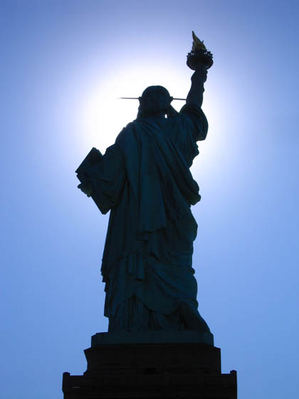 Standing behind the Statue of Liberty as the sun hides behind her face on a winter morning.