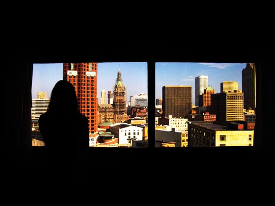 A view from the Hyatt of downtown Milwaukee and a girl's silhouette.