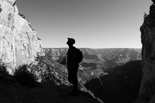 A hiker in the Grand Canyon taking in the amazing view as he descends into the canyon.