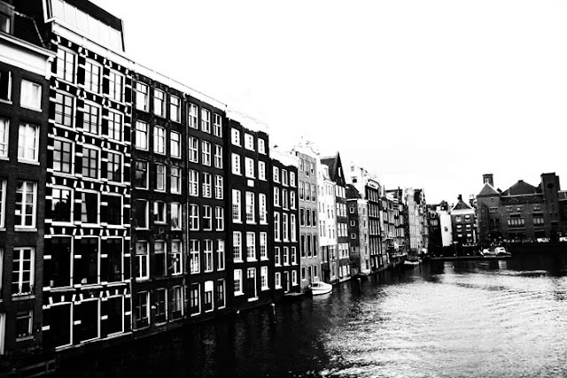 A wide Amsterdam canal near Amsterdam Centraal Station.