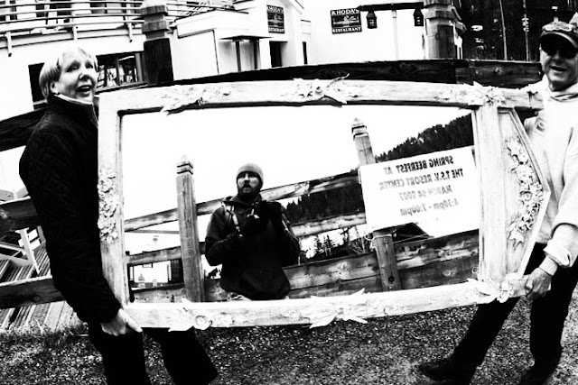 A photographer's reflection in a big mirror that two people are carrying through the village in Taos, New Mexico.