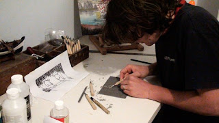 Noferin at work in studio. Carving a lino print.