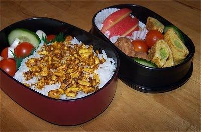 Bento mit Apfel, Tomate, Gurke, Reis, Erdnuss-Curry-Furikake, Mini-Fleischklößchen und Tamagoyaki mit Frühlingszwiebel.