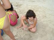 Andressa fazendo bolinho de areia.
