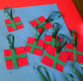 toddler gluing ribbon on hand made Christmas ornament