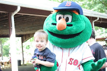 Nathan holding his green monster while being held by the Green Monster of the Red Sox