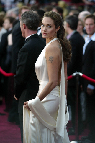 Angelina Jolie having small dragon tattoo on her upper arm.