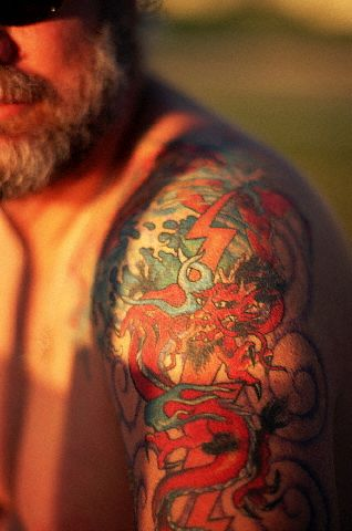 Red dragon and thunder tattoo on bearded male's upper arm.