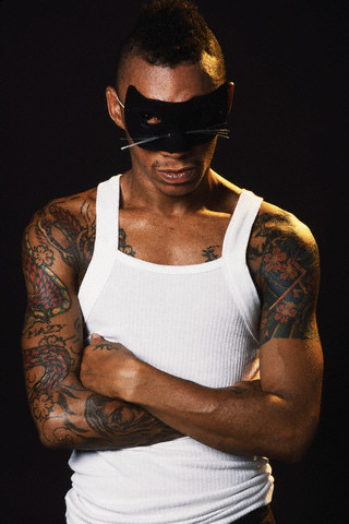 Black man with a mask, having sleeve dragon tattoo to chest.