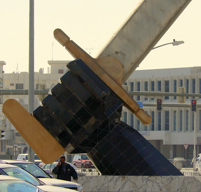 A giant hand clutches the hilt of a sword in Grand Hamad Street