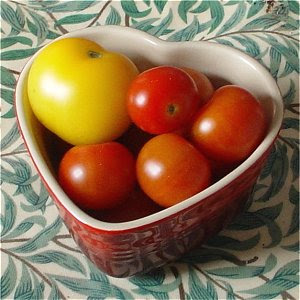 Red tomatoes and a yellow tomato in a heart-shaped dish