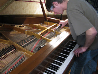 Joshua Hammond repairing broken strings on the Hastings' piano