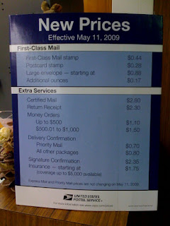 new prices of postage stamps on a sign at a post office