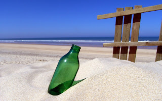 Groene fles in het zand