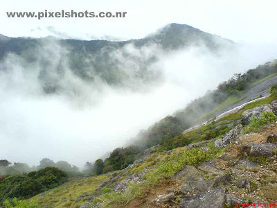 mist in munnar covering the mountains,a scenery of munnar mountains in mist photographed from rajamala munnar kerala
